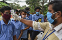 School children wearing masks get their hands sanitized and temperatures checked as they arrive to appear for state board examination during the coronavirus pandemic in Kochi, Kerala state, India, Tuesday, May 26, 2020. (AP Photo/R S Iyer)