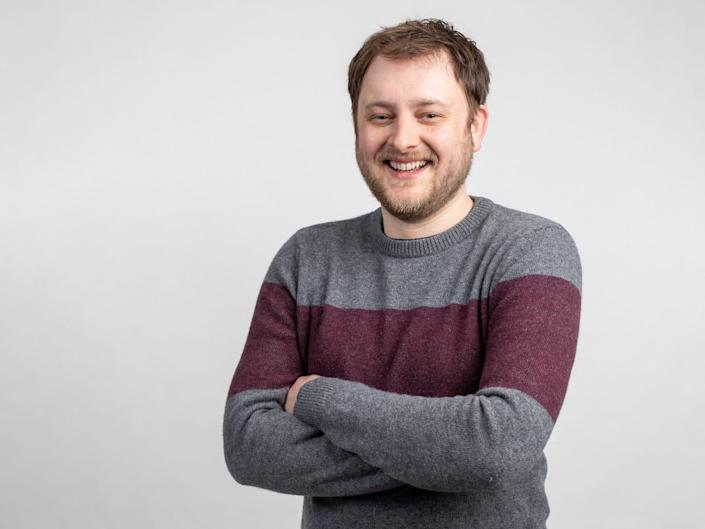 twitch executive lewis mitchell smiles with arms folded against light gray backdrop