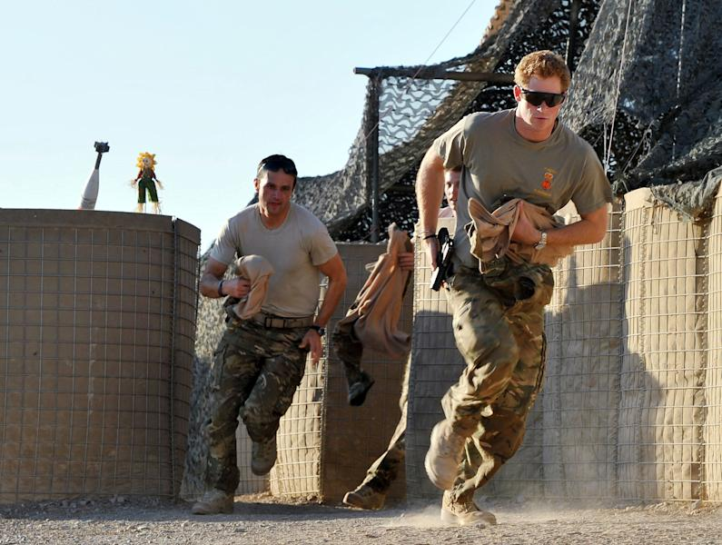 FILE - In this Nov. 3, 2012 file photo, Britain's Prince Harry, right, or just plain Captain Wales as he is known in the British Army, races out from the VHR (very high readiness) tent to scramble his Apache with fellow pilots, during his 12-hour shift at the British-controlled flight-line in Camp Bastion southern Afghanistan. During Prince Harry's 20-week deployment in Afghanistan, he served as an Apache helicopter pilot with the Army Air Corps. (AP Photo/ John Stillwell, Pool, File)