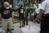 Police officers spray fire extinguisher as pro-democracy activists burn a letter near a flag raising ceremony in Hong Kong, Thursday, Oct. 1, 2020 to mark the China's National Day. (AP Photo/Kin Cheung)