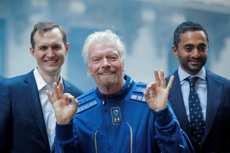 FILE PHOTO: Virgin Galactic co-founder Sir Richard Branson, CEO George Whitesides and Social Capital CEO Chamath Palihapitiya pose together outside of the NYSE as Virgin Galactic (SPCE) begins public trading in New York