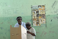 An elderly woman, right, gets help by a relative to mark her ballot during the presidential election in Santo Domingo, Dominican Republic, Sunday May 20, 2012. (AP Photo/Manuel Diaz)