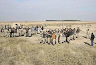 """In this Wednesday, Feb. 1, 2017 photo, Nineveh police forces train with Spanish coalition members at Basmaya base 40 kilometers southeast of Baghdad, Iraq. The U.S.-led coalition is planning for the day Iraq will be free of the Islamic State group, ramping up the training of a future Mosul police force -- even as the battle for the city is temporarily on hold. The security forces are expected to move into villages of Ninevah province around Mosul and into parts of the city recently retaken from IS. The Iraqi military declared Mosul's eastern half """"fully liberated"""" in January and is now preparing to battle for the city's western sector. (AP Photo/Karim Kadim)"""