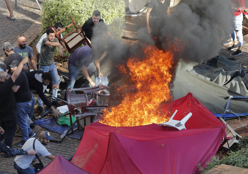 FILE - In this Tuesday, Oct. 29, 2019 file photo, supporters of the Shiite Hezbollah group burn tents in the camp set up by anti-government protesters near the government palace, in Beirut, Lebanon. Lebanon's protests have brought out people from across the country's spectrum of faiths and communities trying to throw out the entire ruling elite. They give a glimpse into a Lebanon transcending longtime divisions among Muslims, Christians and other sects. (AP Photo/Hussein Malla, File)