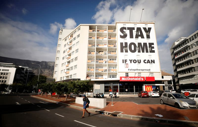 FILE PHOTO: A man walks past a poster covering the side of a building ahead of a 21 day lockdown aimed at limiting the spread of coronavirus disease (COVID-19), in Cape Town