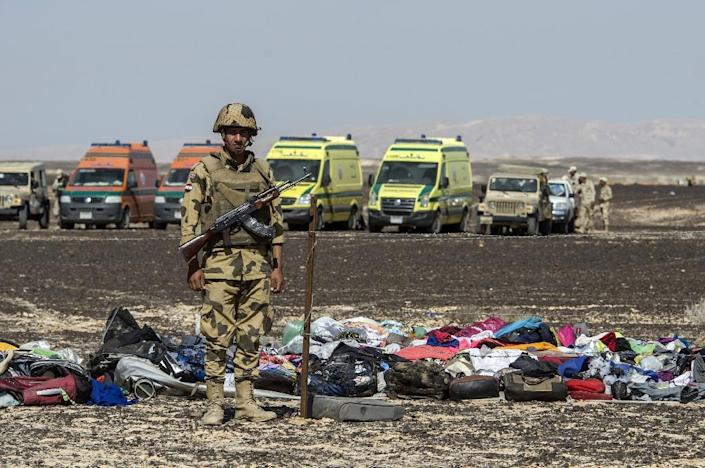An Egyptian soldier stands guard next to the luggage and belongings of passengers of the crashed Russian airliner in Wadi al-Zolomat, a mountainous area in the Sinai Peninsula on November 1, 2015 (AFP Photo/Khaled Desouki)