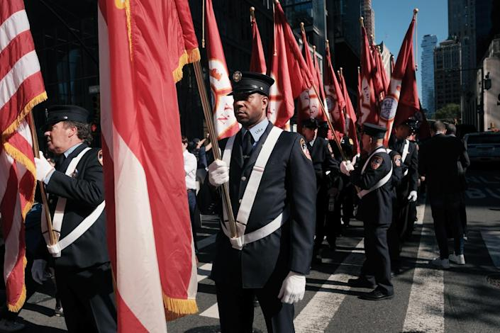 Firefighters in dress uniform gather in lower Manhattan carrying flags.