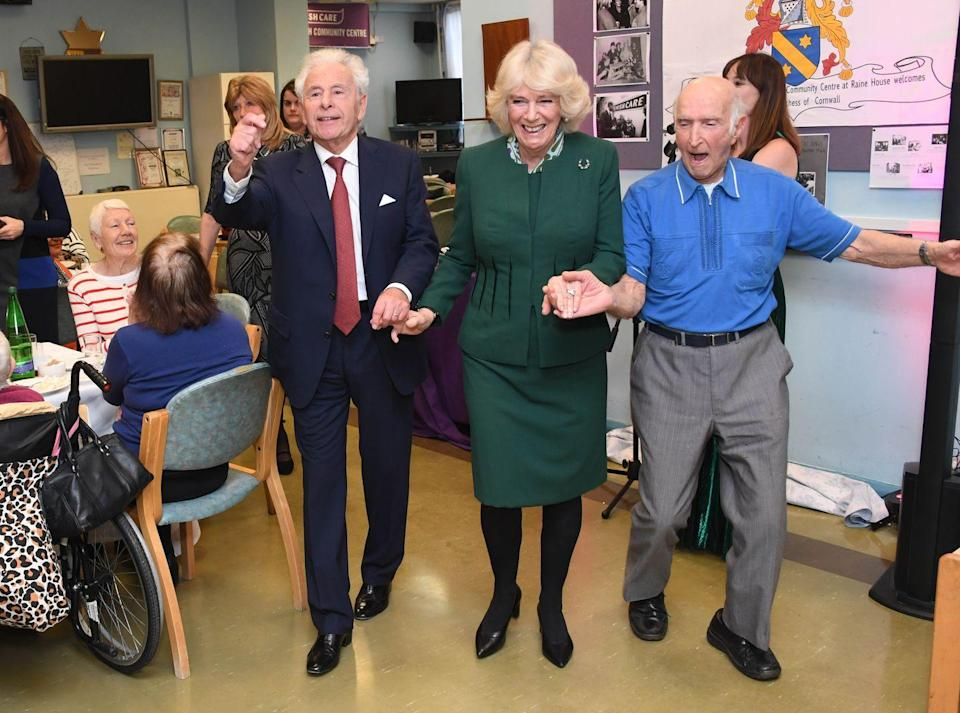 <p>Camilla accessorized her dark green dress suit with a brooch and printed scarf for her visit to the Jewish Care's Brenner Center in Stepney, East London. </p>