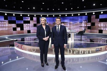 Candidates for the 2017 presidential election, Emmanuel Macron, head of the political movement En Marche !, or Onwards !, and Marine Le Pen, of the French National Front (FN) party, pose prior to the start of a debate in La Plaine-Sainte-Denis