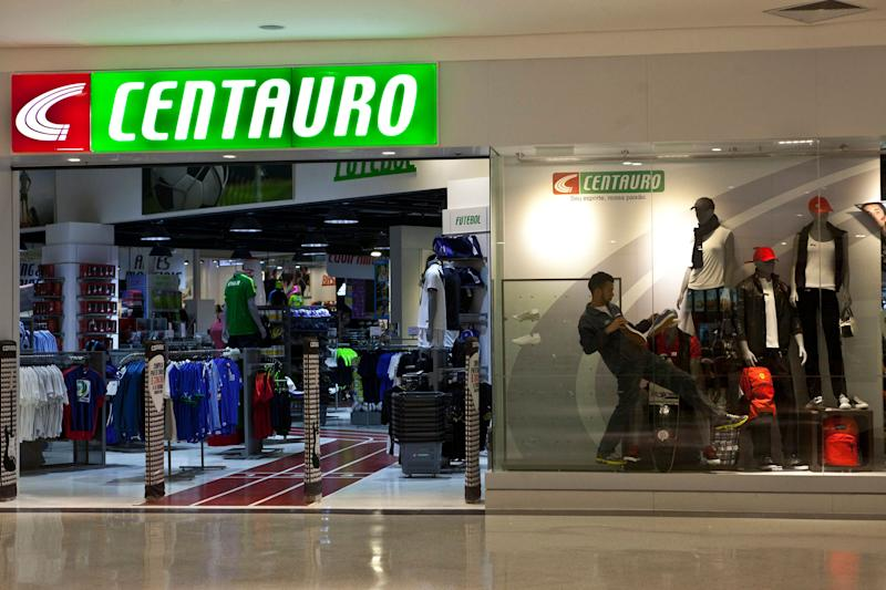 a2410bf6e An employee sets up a window display at Centauro sports store in the  Conviva Americas mall