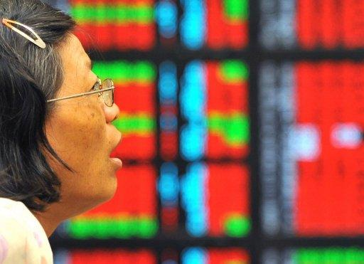 A woman looks at an electronic stock display board at a securities trading house in Taipei