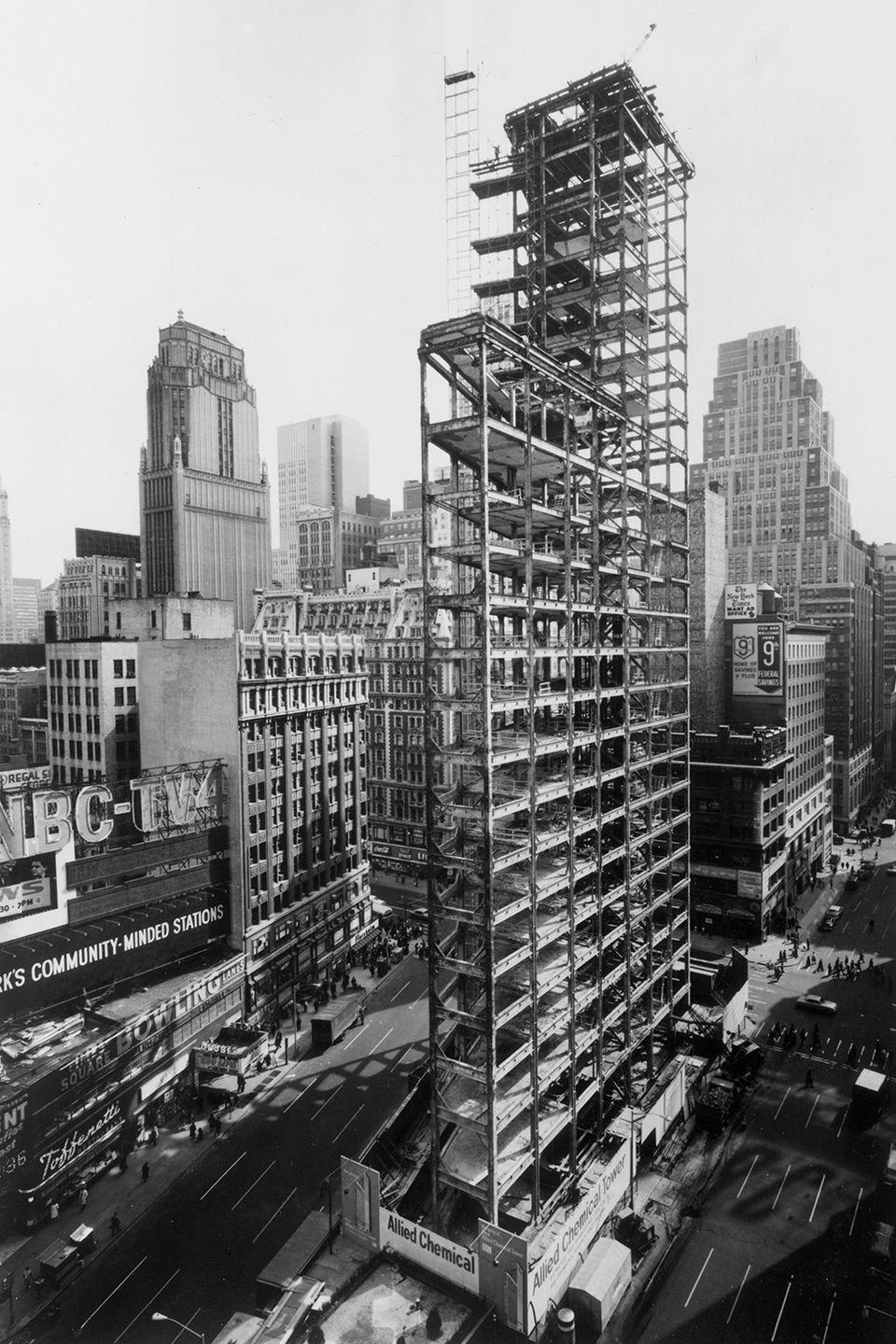 <p>Full-length view of the Allied Chemical Tower reduced to its steel framework during renovation in Times Square.</p>