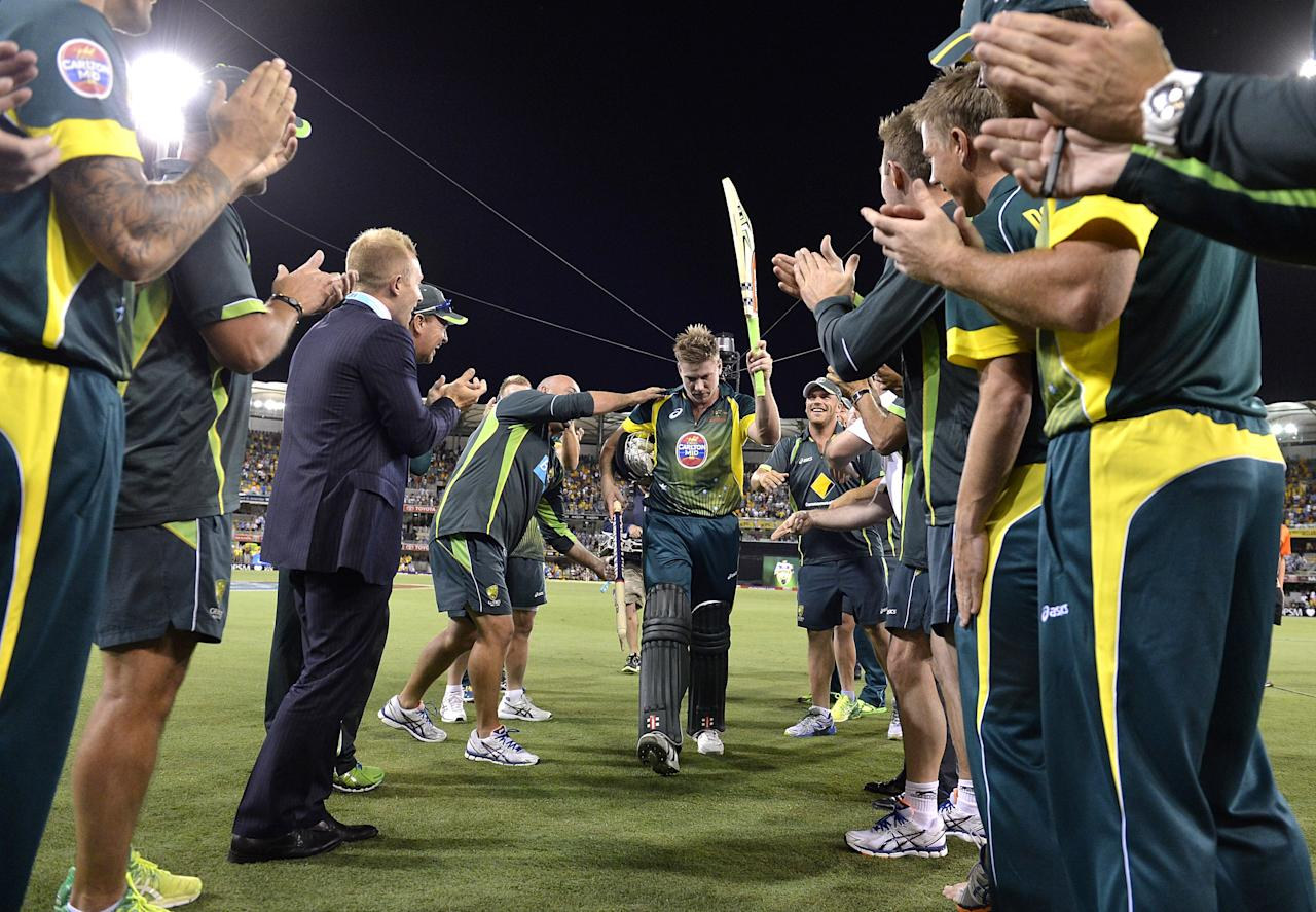 BRISBANE, AUSTRALIA - JANUARY 17:  James Faulkner of Australia is cheered off by team mates after hitting the winning runs after the second game of the One Day International Series between Australia and England at The Gabba on January 17, 2014 in Brisbane, Australia.  (Photo by Bradley Kanaris/Getty Images)