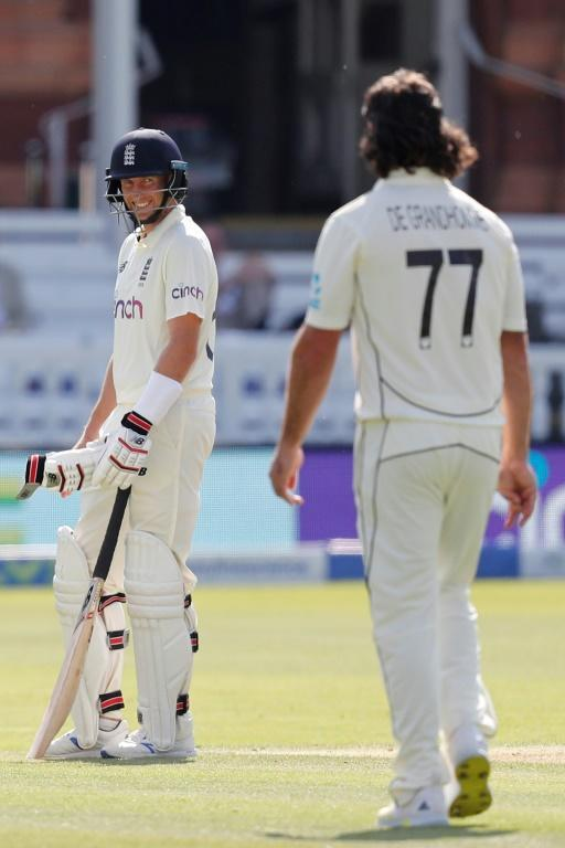 Contest - England captain Joe Root smiles at New Zealand's Colin de Grandhomme (R) after taking a blow on the gloves during the second day of the first Test at Lord's on Thursday