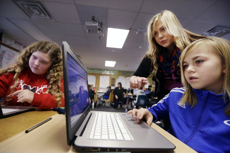 A computer science teacher, center, helps fifth grade students learn programming. AP Photo/Elaine Thompson