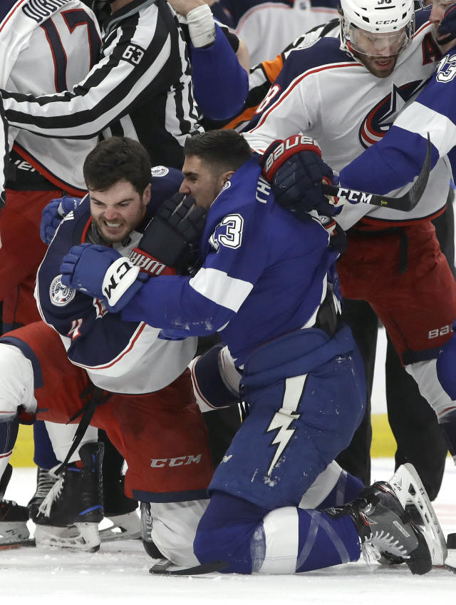 Tampa Bay Lightning center Cedric Paquette (13) and Columbus Blue Jackets defenseman Scott Harrington (4) scrap during the first period of Game 1 of an NHL Eastern Conference first-round hockey playoff series Wednesday, April 10, 2019, in Tampa, Fla. (AP Photo/Chris O'Meara)