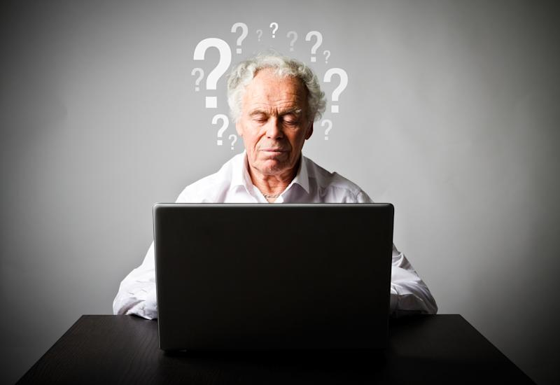 A senior man working on a laptop in front of a wall with question marks drawn on it.