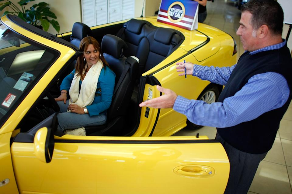 Freddy Melayes shows a new Saab to Karen Cossio at the Deel Saab dealership in Miami. (Photo: Joe Raedle/Getty Images)