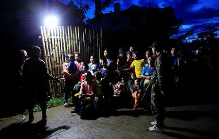 Government troops stands on guard in front of residents who want to leave Marawi city after government troops' continuous assault with insurgents from the so-called Maute group, who has taken over large parts of the city, in Marawi City, Philippines May 26, 2017. REUTERS/Romeo Ranoco