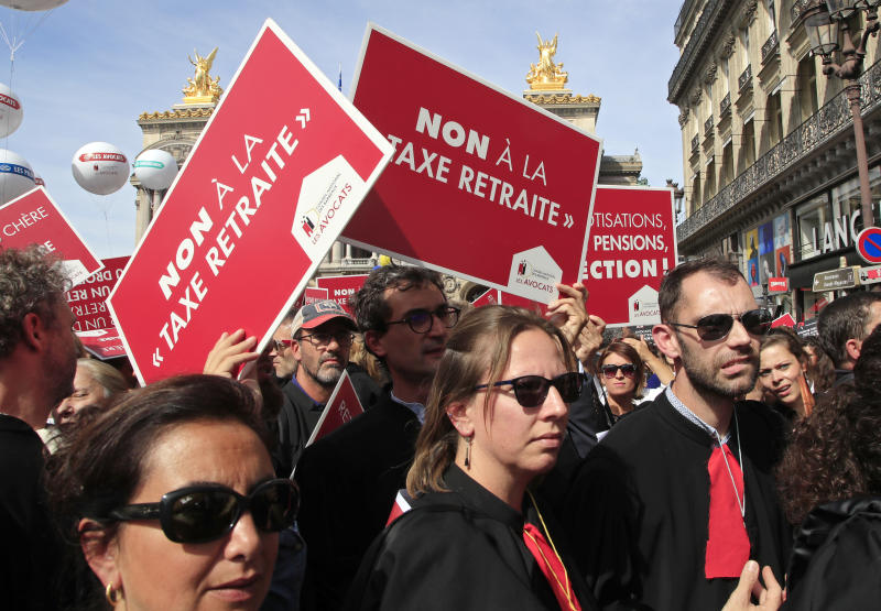 """Lawyers march during a protest against the planned pension change in Paris, Monday, Sept. 16, 2019. French lawyers, doctors, nurses, pilots and others are taking to the streets of Paris to protest planned pension changes by French President Emmanuel Macron's government. Placard read, """"no to the pension tax"""". (AP Photo/Michel Euler)"""
