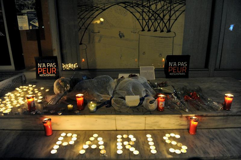 """Flowers and candles reading """"Paris"""" are pictured outside the French consulate in Thessaloniki, Greece on November 14, 2015 (AFP Photo/Sakis Mitrolidis)"""