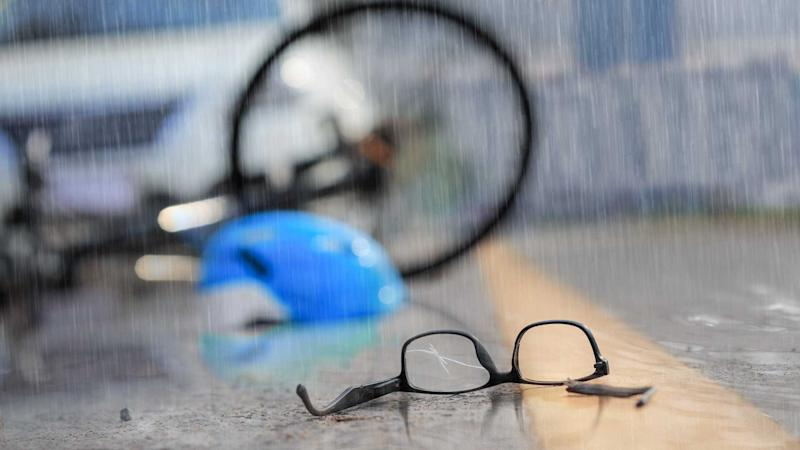 Car accident with bicycle on road in rainy weather