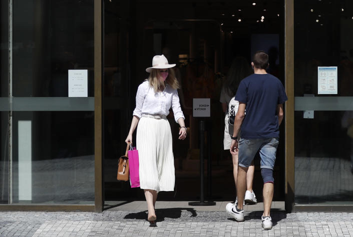 A woman walks out of a shop in Prague, Czech Republic, Monday, May 10, 2021. The Czech Republic is massively relaxing its coronavirus restrictions as the hard-hit nation pay respect to nearly 30,000 dead. Monday's wave of easing came after the new infections fell to the levels unseen from August when the government failed to react in time to an opposite trend, the growing numbers of infected which later contributed to record numbers of deaths. (AP Photo/Petr David Josek)