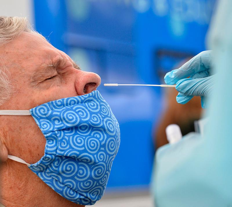 Allan Turner, 72, gets swabbed as part of a COVID-19 test, Sept. 29, 2020, outside the John Horan Apartments in Erie, Pa. The free coronavirus tests were provided by Latino Connection, a Harrisburg-based Latino and minority outreach company.