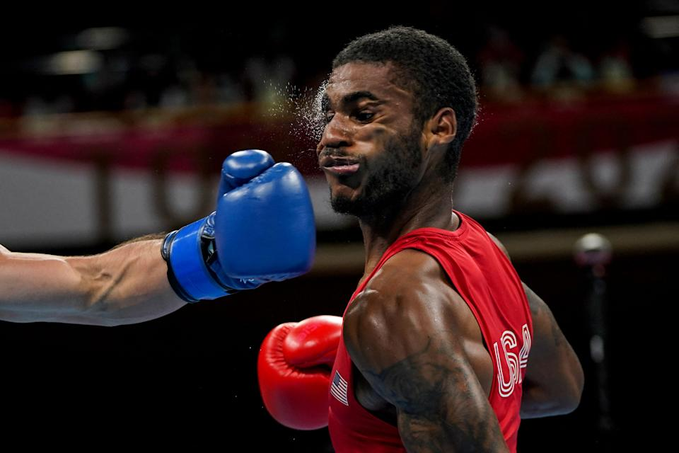 <p>USA's Delante Marquis Johnson (red) takes a punch from Argentina's Brian Agustin Arregui during their men's welter (63-69kg) preliminaries boxing match during the Tokyo 2020 Olympic Games at the Kokugikan Arena in Tokyo on July 24, 2021. (Photo by Frank Franklin II / POOL / AFP) (Photo by FRANK FRANKLIN II/POOL/AFP via Getty Images)</p>