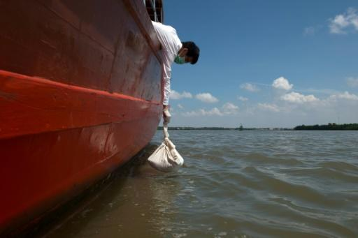 A medical student lowers a bag containing the remains of cadavers into the river