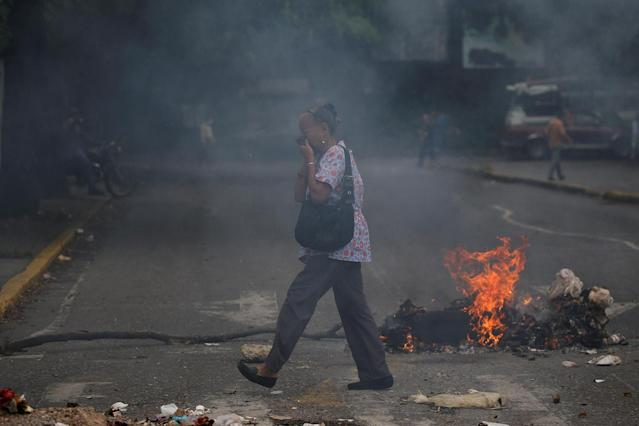 <p>A woman covers her face as she walks past a burning barricade during a protest against Venezuela's President Nicolas Maduro's government in Caracas, Venezuela May 2, 2017. (Photo: Carlos Garcia Rawlins/Reuters) </p>