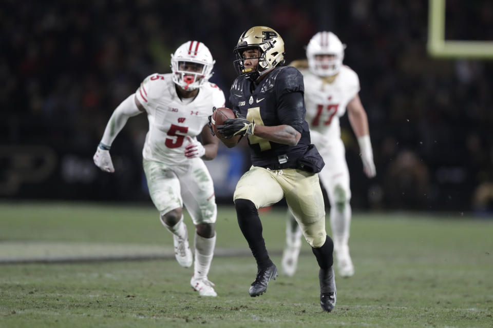 Purdue wide receiver Rondale Moore (4) makes a catch in front of Wisconsin cornerback Rachad Wildgoose (5) on his way to a touchdown during the second half of an NCAA college football game in West Lafayette, Ind., Saturday, Nov. 17, 2018. Wisconsin defeated Purdue 47-44 in overtime. (AP Photo/Michael Conroy)