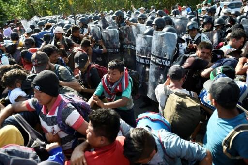 Members of the Mexican National Guard scuffle with Central American migrants - mostly Hondurans heading in a caravan to the US - in Ciudad Hidalgo, Chiapas State on Thursday
