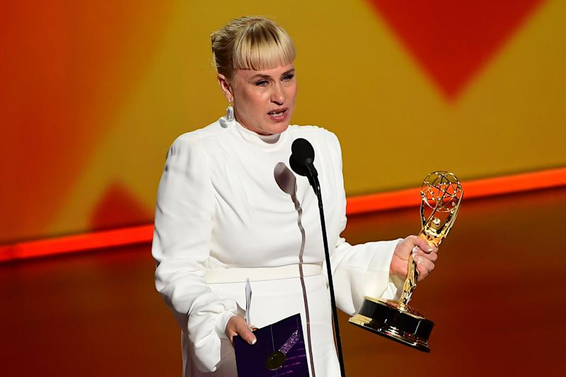 Patrcia Arquette stands on stage talking into a microphone and holding an Emmy Award