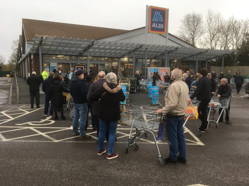 Early shoppers queue and wait in line for the opening of a supermarket in Rugby, England, Thursday, March 19, 2020. According to the World Health Organization, most people recover in about two to six weeks, depending on the severity of the illness. Some supermarkets are limiting the number of similar items shopper can buy to try and halt hoarding and panic buying, when the supermarket groups and government say there is no shortages in the supply chain. (AP Photo/Martin Cleaver)