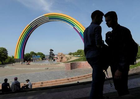 "People gather near the Soviet monument, ""Arch of the Friendship of Nations"", which is painted with rainbow colours, in celebration of diversity ahead of the Eurovision Song Contest, in central Kiev, Ukraine May 4, 2017. REUTERS/Gleb Garanich"