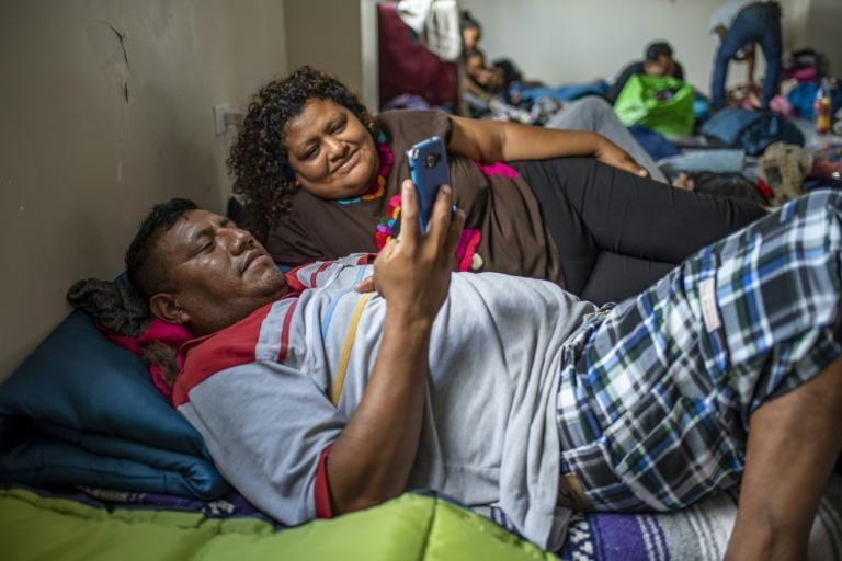 Eloy Camarillo Salazar and Saturina Patricio Gonzales pass the time by watching a video at the Matamoros migrant shelter