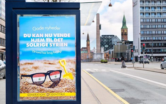 """The poster at a bus stop shows a pair of sunglasses reflecting the Syrian flag on a beach and tells refugees they can """"go home to sunny Syria"""""""
