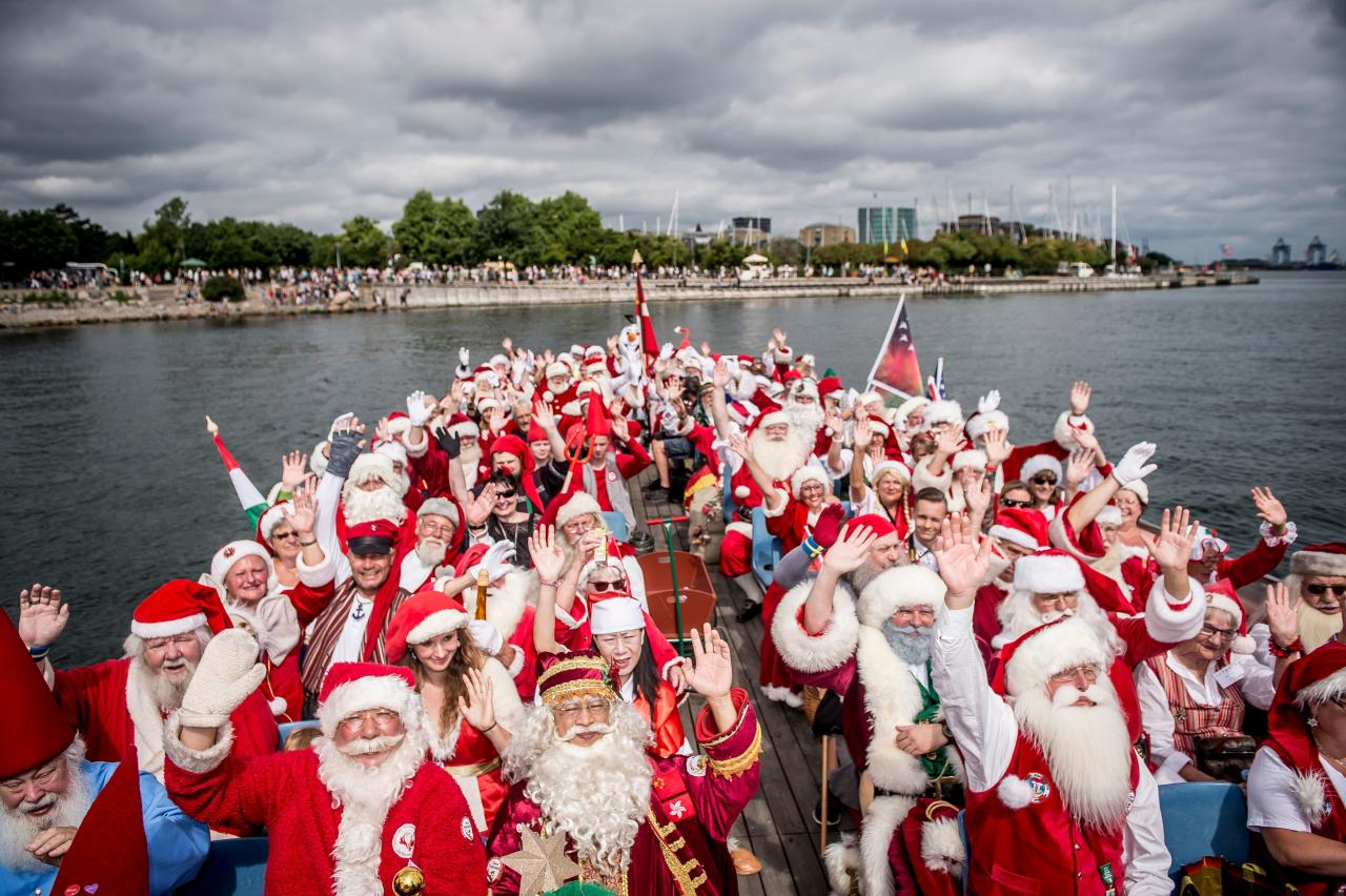 <p>People dressed as Santa Claus wave as they take part in a canal tour that is part of the annual World Santa Claus congress on July 23, 2018 in Copenhagen. (Photo: Mads Claus Rasmussen/Ritzau Scanpix/AFP/Getty Images) </p>