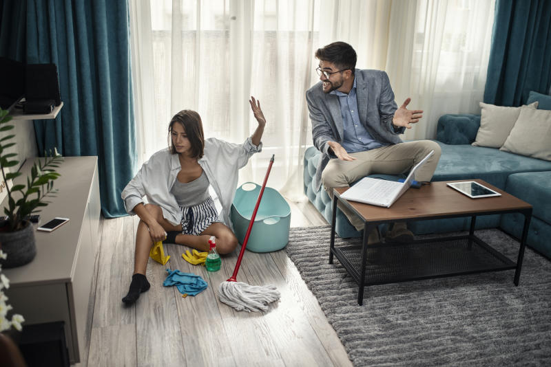 Woman cleans the floor at home while her lazy man sits on the couch and uses a laptop