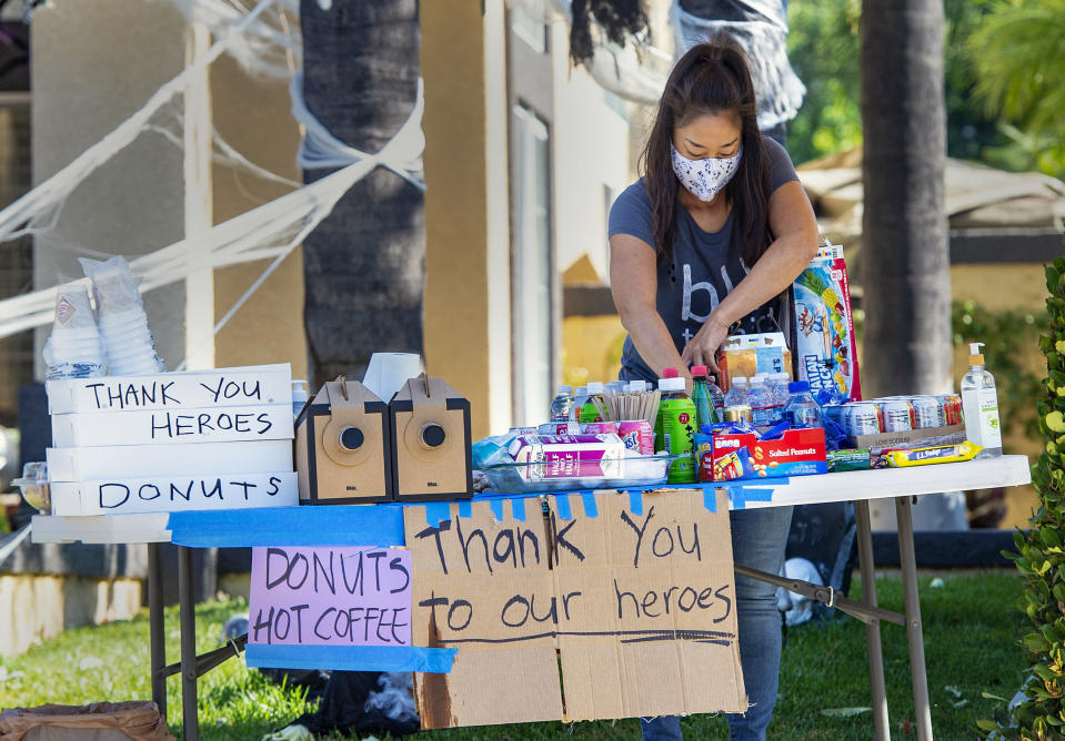Naeko Karst mans a table of food and drinks for firefighters working the Silverado Fire in front of her home on Viaggio Lane in Foothill Ranch, Wednesday, Oct. 28, 2020. (Mark Rightmire/The Orange County Register via AP)