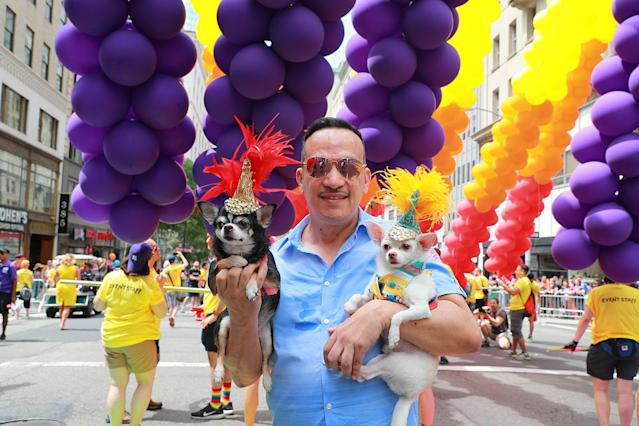 <p>A man carries his dogs, Bogey and Kimba — suitably adorned with festive headdresses — during the N.Y.C. Pride Parade in New York on June 25, 2017. (Photo: Gordon Donovan/Yahoo News) </p>