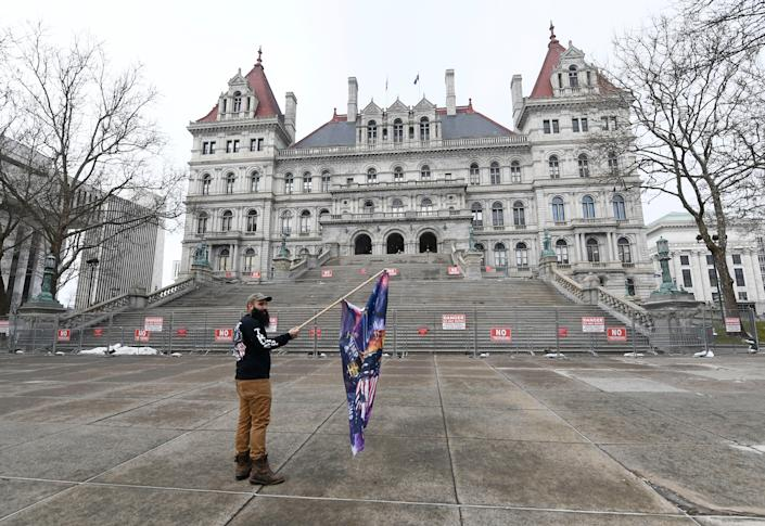 <p>Trump supporter Mark Leggiero, of Florida, N.Y., holds a banner outside the New York state Capitol objecting the inauguration of President Joe Biden on Wednesday 20 January 2021, in Albany, N.Y</p> ((Associated Press))