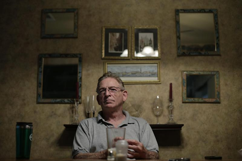 In this June 21, 2013, photo, Phillip Baker listens as family members talk about his wife Debra Masters Baker, in Austin, Texas. Debra Masters Baker was killed in her home Jan. 13, 1988. Her slaying remains unsolved but the family believes it might never have occurred had authorities not focused on the wrong man in a similar killing 17 months earlier. (AP Photo/Eric Gay)