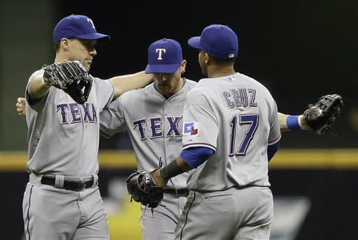 Texas Rangers' David Murphy, from left, Craig Gentry and Nelson Cruz (17) celebrate after a baseball game against the Milwaukee Brewers Wednesday, May 8, 2013, in Milwaukee. The Rangers won 4-1. (AP Photo/Morry Gash)