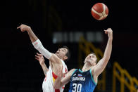 Spain's Alberto Abalde fights for a rebound with Slovenia's Zoran Dragic (30) during a men's basketball preliminary round game at the 2020 Summer Olympics, Sunday, Aug. 1, 2021, in Saitama, Japan. (AP Photo/Charlie Neibergall)