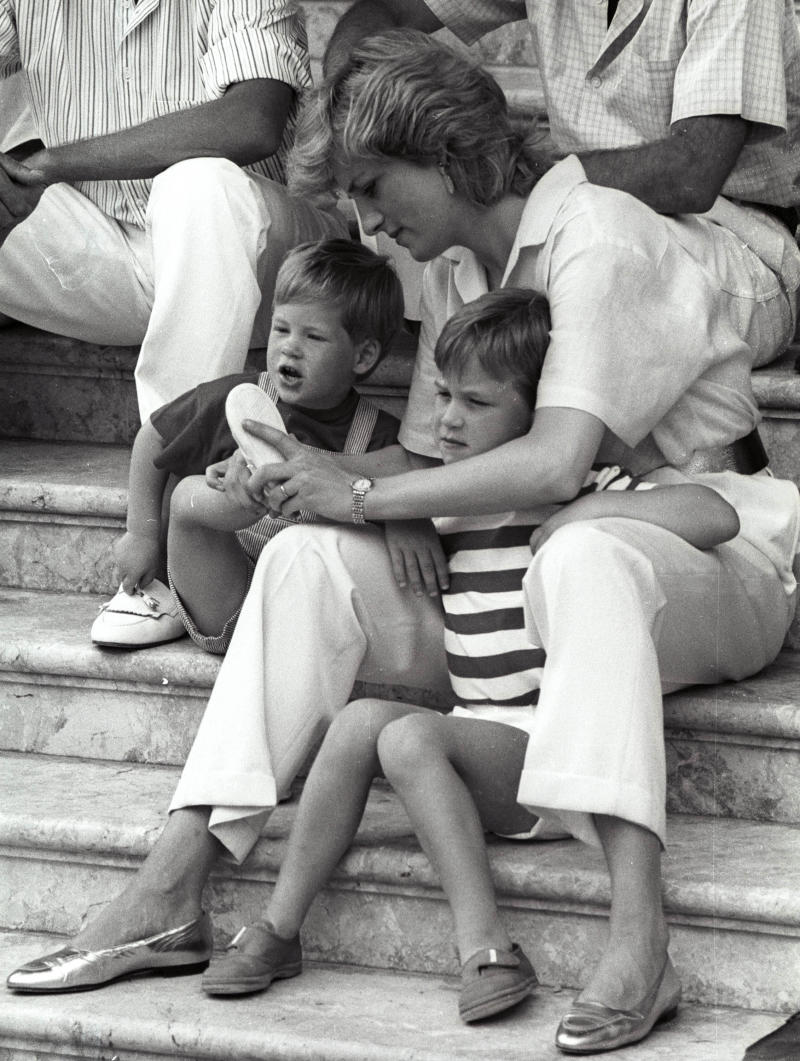 Princess Diana puts on shoes for little Prince Harry as her other son Prince William squints from the bright sun on August 9, 1988, during their vacation with the Spanish royal family at Marivent Palace in Palma De Mallorca. REUTERS/Hugh Peralta
