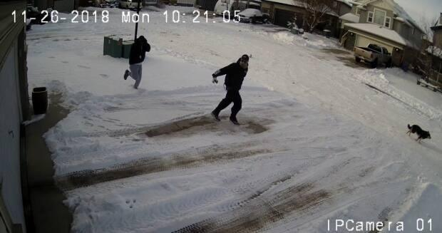 Two men are shown in a still image from security camera footage fleeing the scene after Dennis Lewis, 41, was shot dead in his home in Chestermere, Alta., on Nov. 26, 2018.  (RCMP - image credit)