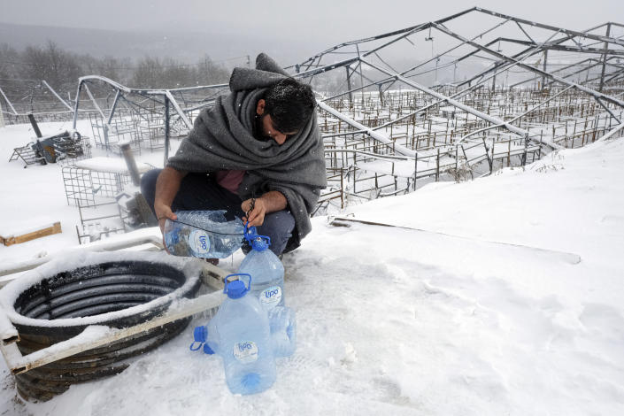 A migrant uses plastic bottles to take water out of a well during a snowfall at the Lipa camp, outside Bihac, Bosnia, Monday, Jan. 11, 2021. Aid workers say migrants staying at a camp in northwestern Bosnia have complained or respiratory and skin diseases after spending days in make-shift tents and containers amid freezing weather and snow blizzards. Most of the hundreds of migrants at the Lipa facility near Bosnia's border with Croatia on Monday have been accommodated in heated military tents following days of uncertainty after a fire gutted most of the camp on Dec. 23. (AP Photo/Kemal Softic)