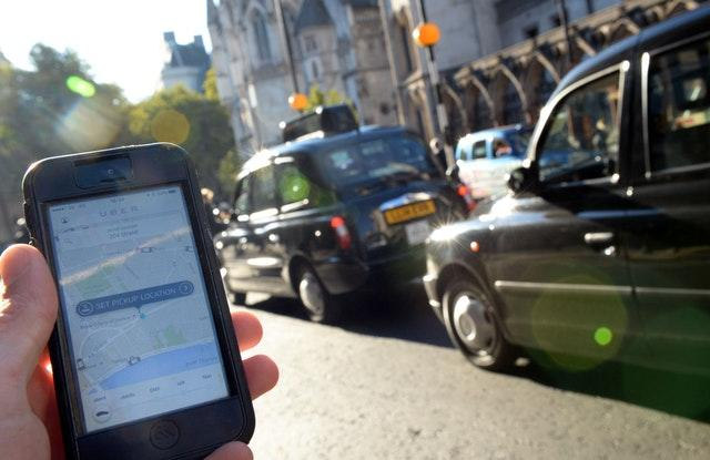 A man holds a smartphone displaying the Uber app (Anthony Devlin/PA)